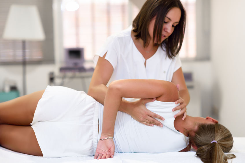Professional female physiotherapist giving shoulder massage to blonde woman in hospital. Medical check at the shoulder in a physiotherapy center.